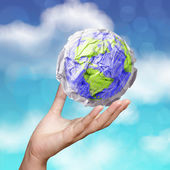 Hand showing crumpled world paper symbol as concept on blue sky  — Stock Photo