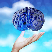Medical doctor hand showing 3d blue glass human brain on nature  — Stock Photo