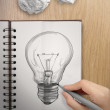 Hand with a pen drawing light bulb on note book as concept — Stock Photo #51377433