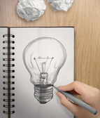 Hand with a pen drawing light bulb on note book as concept — Stock Photo