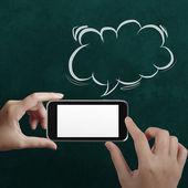 Hand using mobile phone with speech bubble on chalkboard — Stock Photo