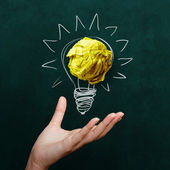 Hand holding crumpled paper with Light bulb on blackboard backgr — Stock Photo