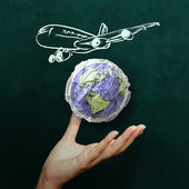 Hand showing airplane with crumpled world paper symbol as concep — Stock Photo