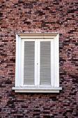 Brick wall with white vintage window — Stock Photo