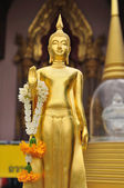 Gold standing Buddha statue with jasmine wreath — Stock Photo