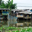 Stock Photo: Slum houses near canal