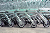 Row of empty shopping carts in big supermarket — Stock Photo