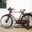 Stock Photo: Oldie bicycles are leaned in front of white wall,