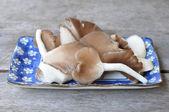 Mushrooms sliced in blue plate — Stock Photo