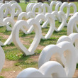 Foto Stock: Many white heart arrange on green yard