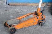 Short orange screw jack on concrete — Foto Stock