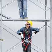 Unidentified workers on iron scaffolding — Stockfoto