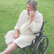 Stock Photo: Elderly min wheelchair with cell phone