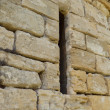 Arrow slit in medieval wall - Stock Photo
