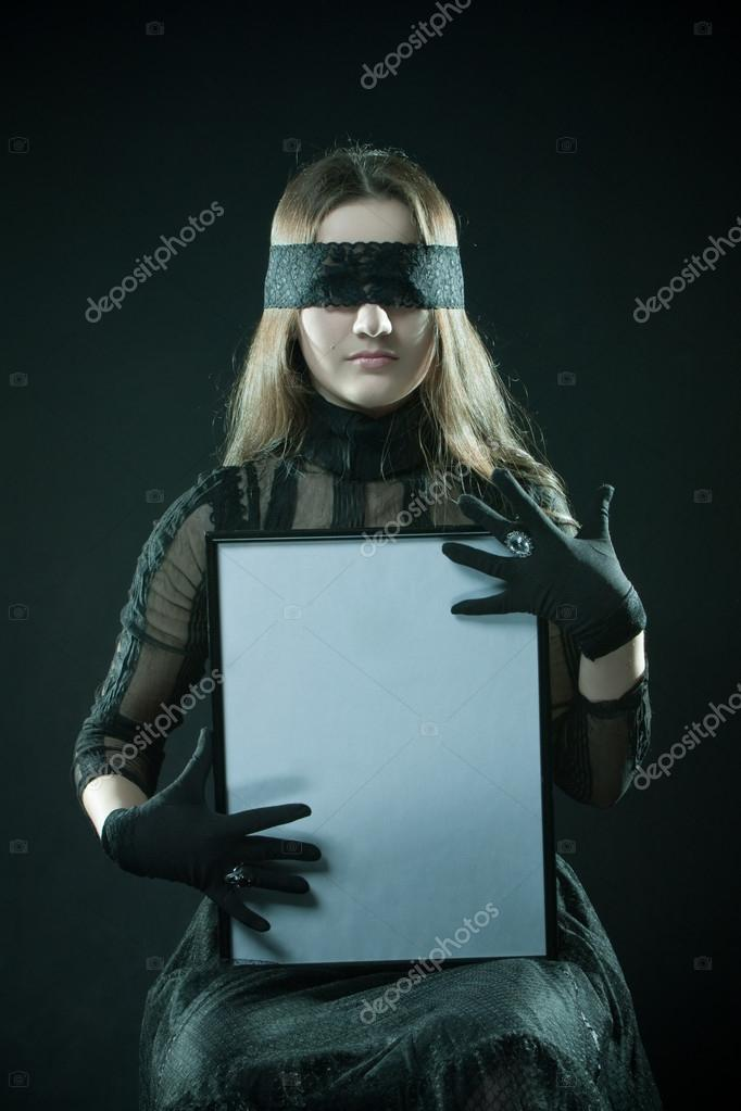 Pretty gothic girl in black dress with blank frame in hands over dark background — Photo #17019607