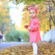 Foto Stock: Little girl eating apple on background of autumn