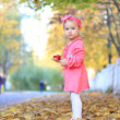图库照片: Little girl eating apple on background of autumn