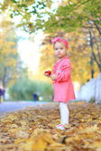 Little girl eating an apple on a background of autumn — Stok fotoğraf