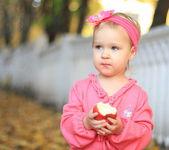Kleines mädchen einen apfel zu essen — Stockfoto