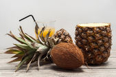 Coconut and half-cut pineapple on wooden board — Stock Photo