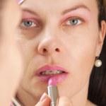 Putting on lip gloss — Stock Photo