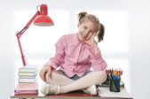 Girl with glasses sitting on a desk — Stock Photo