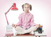 Schoolgirl meditating on the desk — Stock Photo