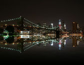 Brooklyn Bridge by night reflect in east river and new york skyline. freedom tower — Stock Photo
