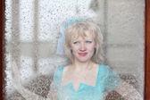 Mooi meisje in een blauwe jurk ziet er in een venster van de sneeuw — Stockfoto