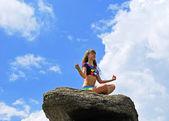 Beautiful girl meditates on the big boulder — Stock Photo