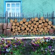 Stock Photo: Woodpile near wooden fence and pansies