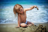 Сute girl playing in sand — Stock Photo