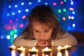 Small girl looking at burning candles — Stock Photo