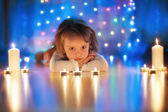 Small girl lying on the floor and looking at candles — Stock Photo