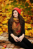 Woman in red cap sitting in park — Stock Photo