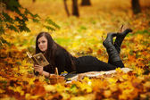 Young woman reading book in park — Stock Photo