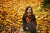 Woman sitting on plaid in park — Stock Photo