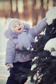 Girl touching fir-tree — Stock Photo