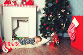 Girl laying under Christmas tree — Stock Photo