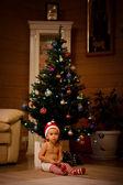 Girl sitting under Christmas tree — Stock Photo