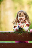 Girl putting hands on fence — Stock Photo