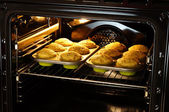 Baking muffins in oven — Stockfoto