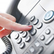 Stock Photo: Female hand dialing a phone number