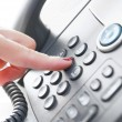 Foto Stock: Female hand dialing phone number
