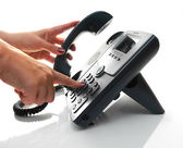 Female hand dialing a phone number with picked up headset — Stock Photo