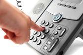 Kobieta ręka jest wybieranie numeru telefonu z zestawem słuchawkowym podniósł — Zdjęcie stockowe