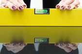 A woman using a spirit level for home work — Stock Photo