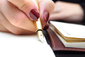Woman is writing in notepad — Stock Photo
