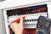 Hand of an electrician with multimeter probe at an electrical sw — Stock Photo