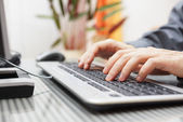 Man  is typing on keyboard at home — Stok fotoğraf